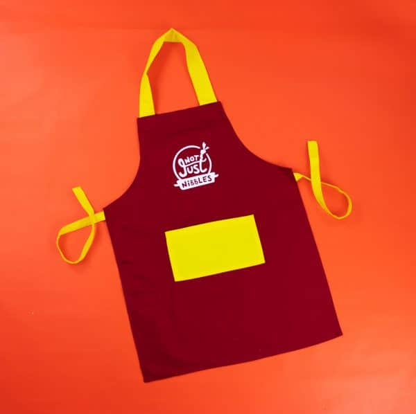 Red with yellow pocket Not Just Nibbles apron